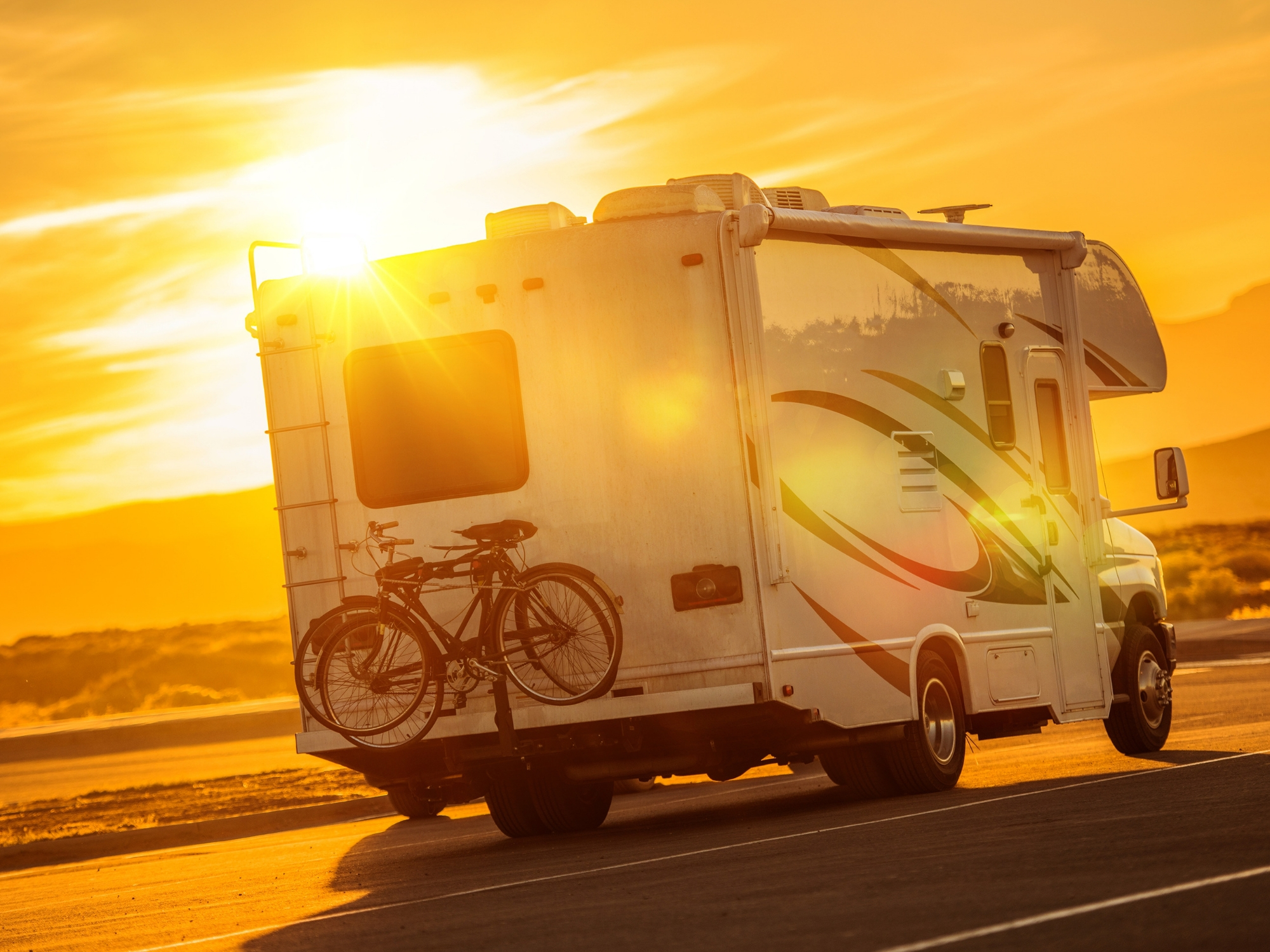 RV with bicycle driving through Sunset
