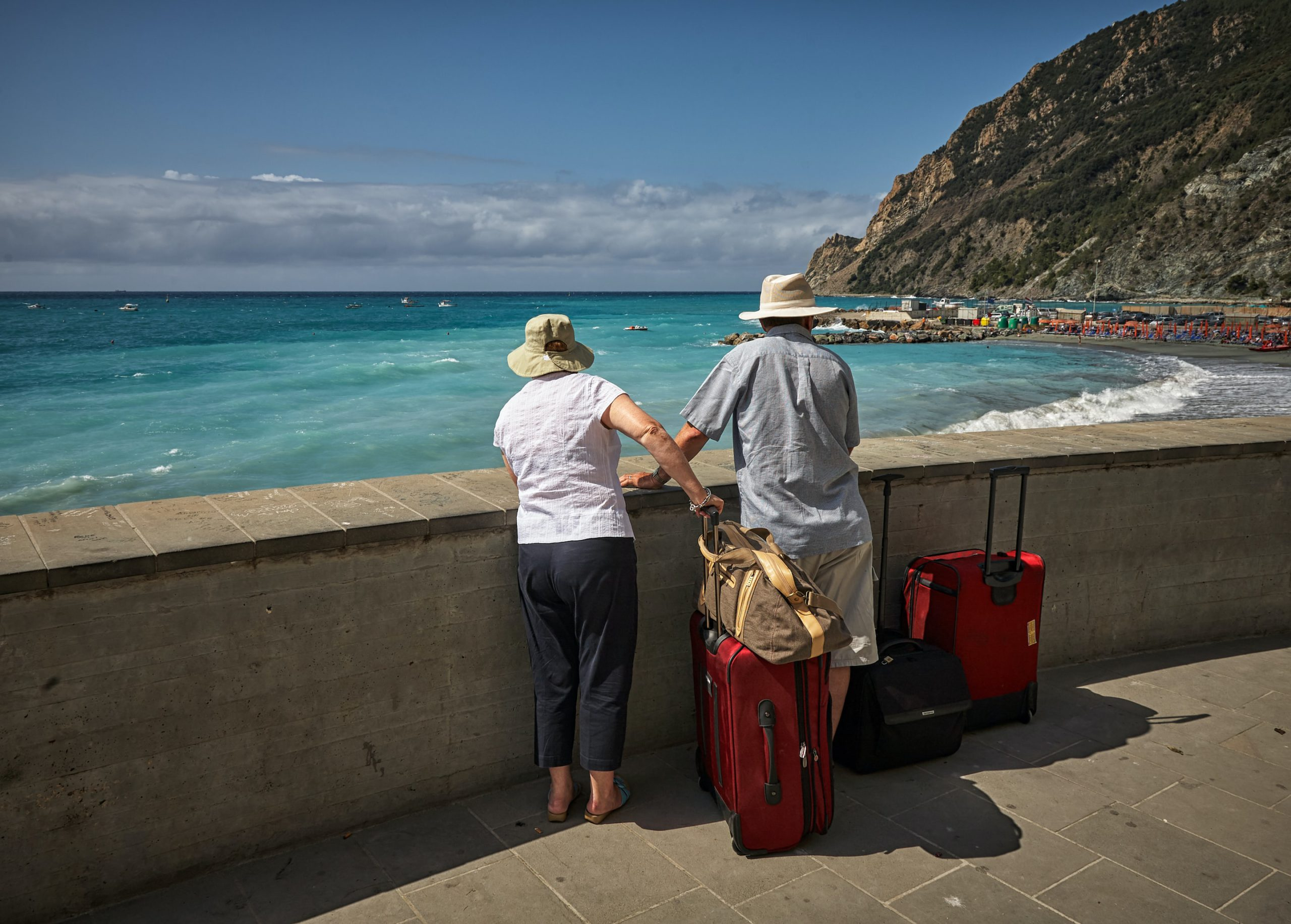 senior travelers with luggage in front of beach